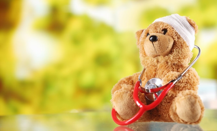 Sick Teddy Bear with Stethoscope on Glass Table